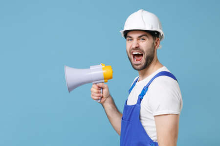Side view of angry young man in coveralls protective helmet hardhat scream in megaphone isolated on blue background studio. Instruments accessories for renovation apartment room. Repair home concept.