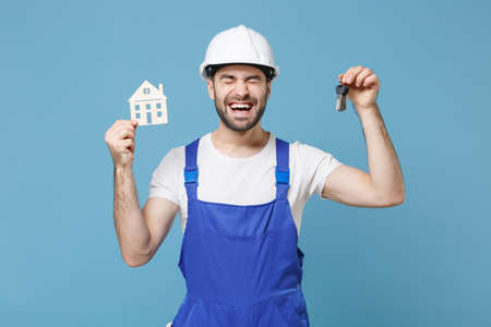 Joyful young man in coveralls protective helmet hardhat hold house bunch of keys isolated on blue wall background in studio. Instruments accessories for renovation apartment room. Repair home concept.