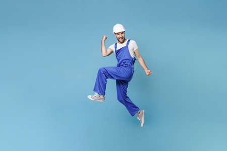 Happy young man in coveralls protective helmet hardhat isolated on blue background studio. Instruments accessories for renovation apartment room. Repair home concept. Jumping, doing winner gesture.