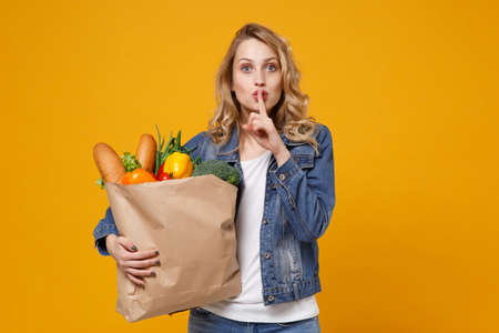 Woman isolated on orange background. Delivery service from shop or restaurant concept. Hold brown craft paper bag for takeaway with food products say hush be quiet with finger on lips shhh gesture. 免版税图像