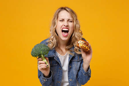 Crazy young woman in denim clothes isolated on yellow orange wall background studio portrait. Proper nutrition, healthy lifestyle, fast food, choice concept. Holding green broccoli burger screaming.