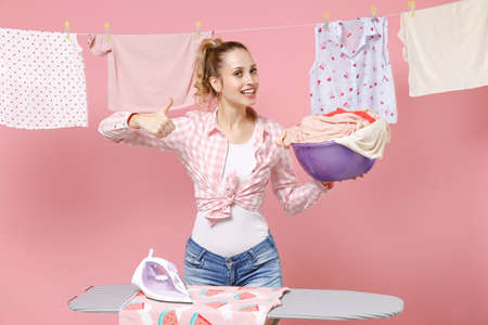 Smiling young woman housewife in checkered shirt dry clothes on rope ironing on board hold basin with clean clothes doing housework isolated on pink background. Housekeeping concept. Showing thumb up.