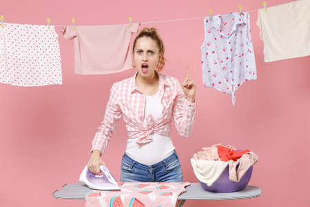 Angry woman housewife in checkered shirt dry clothes on rope ironing clean clothes on board while doing housework isolated on pink background. Housekeeping concept. Pointing index finger up, swearing.