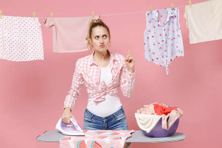 Confused displeased woman housewife in checkered shirt dry clothes on rope ironing clean clothes on board doing housework isolated on pink background. Housekeeping concept. Pointing index finger up. Standard-Bild