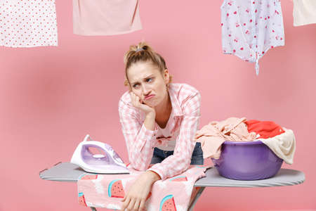 Displeased tired young woman housewife in checkered shirt dry clothes on rope ironing clean clothes on board doing housework isolated on pink background. Housekeeping concept. Put hand prop up on chin