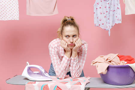 Confused tired young woman housewife in checkered shirt dry clothes on rope ironing clean clothes on board doing housework isolated on pink background. Housekeeping concept. Put hands prop up on chin.