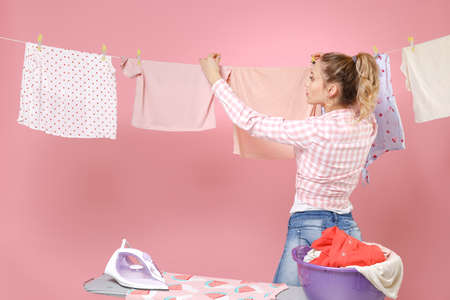 Beautiful young girl housewife in checkered shirt dry clothes on rope ironing clean clothes while doing housework isolated on pink background studio portrait. Housekeeping concept. Mock up copy space. Standard-Bild