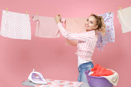 Smiling young woman housewife in checkered shirt dry clothes on rope ironing clean clothes while doing housework isolated on pink background studio portrait. Housekeeping concept. Mock up copy space.