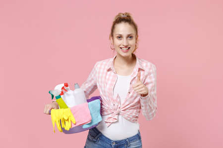 Smiling young woman housewife in checkered shirt hold basin with detergent bottles washing cleansers while doing housework isolated on pink background studio. Housekeeping concept. Showing thumb up. Standard-Bild