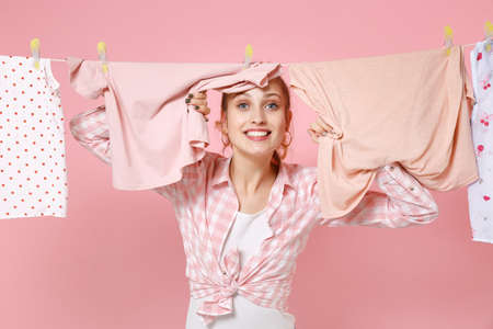 Smiling young woman housewife in checkered shirt dry clothes on rope while doing housework isolated on pastel pink background studio portrait. Housekeeping concept. Mock up copy space. Looking camera.