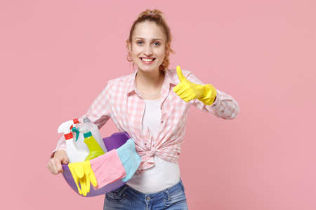 Smiling young woman housewife in rubber gloves hold basin with detergent bottles washing cleansers doing housework isolated on pink background studio portrait. Housekeeping concept. Showing thumb up.