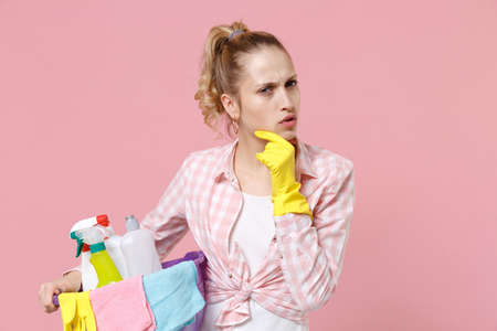 Puzzled young woman housewife in rubber gloves hold basin with detergent bottles washing cleansers doing housework isolated on pink background studio. Housekeeping concept. Put hand prop up on chin.