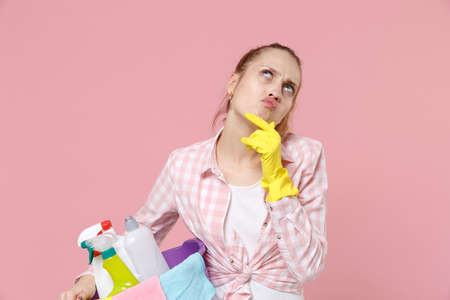 Pensive woman housewife in rubber gloves hold basin with detergent bottles washing cleansers doing housework isolated on pink background. Housekeeping concept. Put hand prop up on chin, looking up. Standard-Bild