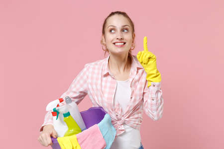 Pensive woman housewife in rubber gloves hold basin with detergent bottles washing cleansers doing housework isolated on pink background. Housekeeping concept. Holding index finger up with great idea. Standard-Bild