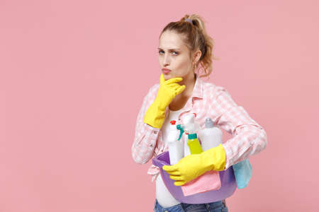 Pensive young woman housewife in rubber gloves hold basin with detergent bottles washing cleansers doing housework isolated on pink background studio. Housekeeping concept. Put hand prop up on chin.