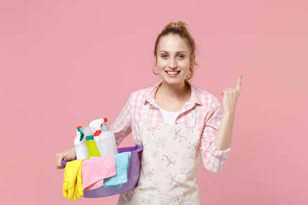 Smiling young woman housewife in apron hold basin with detergent bottles washing cleansers while doing housework isolated on pink background in studio. Housekeeping concept. Pointing index finger up.