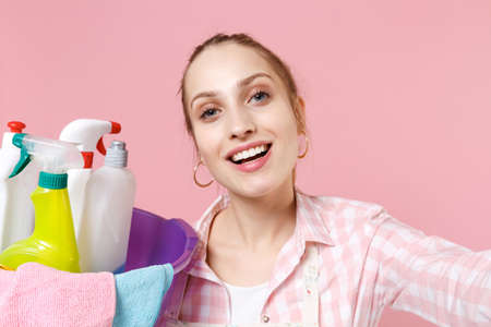 Close up of smiling young woman housewife hold basin with detergent bottles washing cleansers doing housework isolated on pink wall background. Housekeeping concept. Doing selfie shot on mobile phone.