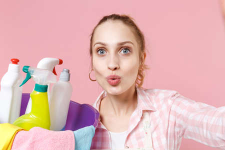 Close up of amazed woman housewife in apron hold basin with detergent bottles washing cleansers doing housework isolated on pink background. Housekeeping concept. Doing selfie shot on mobile phone.