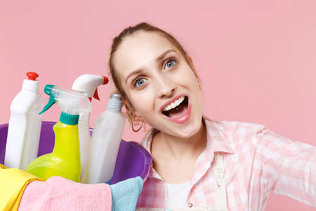 Close up of excited woman housewife in apron hold basin with detergent bottles washing cleansers doing housework isolated on pink background. Housekeeping concept. Doing selfie shot on mobile phone.