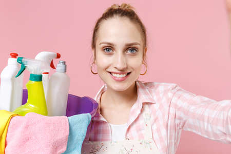 Close up of beautiful woman housewife in apron hold basin with detergent bottles washing cleansers doing housework isolated on pink background. Housekeeping concept. Doing selfie shot on mobile phone.