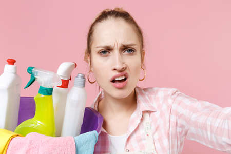 Close up of displeased girl housewife in apron hold basin with detergent bottles washing cleansers doing housework isolated on pink background. Housekeeping concept. Doing selfie shot on mobile phone. Standard-Bild