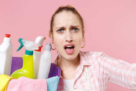 Close up of perplexed woman housewife in apron hold basin with detergent bottles washing cleansers doing housework isolated on pink background. Housekeeping concept. Doing selfie shot on mobile phone.