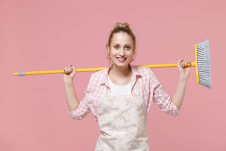 Smiling beautiful young woman housewife in casual clothes, apron doing housework isolated on pastel pink wall background studio portrait. Housekeeping concept. Mock up copy space. Hold in hands broom.