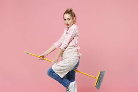 Side view of funny young woman housewife in casual clothes, apron doing housework isolated on pastel pink wall background studio portrait. Housekeeping concept. Mock up copy space. Sitting on broom.