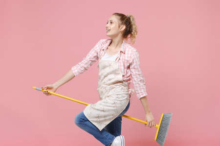 Side view of smiling young woman housewife in casual clothes, apron doing housework isolated on pastel pink wall background studio portrait. Housekeeping concept. Mock up copy space. Sitting on broom. Standard-Bild