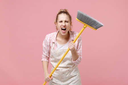 Crazy angry young woman housewife in casual clothes, apron doing housework isolated on pastel pink background studio portrait. Housekeeping concept. Mock up copy space. Hold in hands broom, screaming.