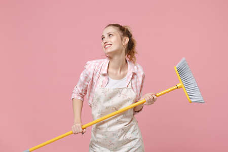 Smiling young woman housewife in casual clothes, apron doing housework isolated on pastel pink background studio portrait. Housekeeping concept. Mock up copy space. Hold in hands broom, looking aside.