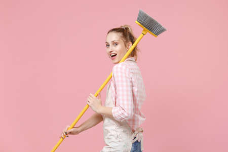 Side view of beautiful young woman housewife in casual clothes, apron doing housework isolated on pastel pink background studio. Housekeeping concept. Mock up copy space. Hold broom, looking camera.