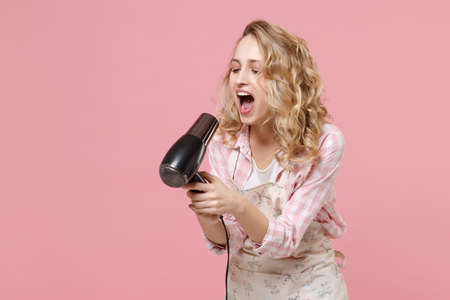 Crazy young woman housewife in casual clothes, apron posing isolated on pastel pink background in studio. Housekeeping concept. Mock up copy space. Blow drying hair, screaming, sing song in hairdryer,