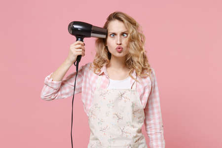 Loony woman housewife in casual clothes, apron posing isolated on pastel pink background. Housekeeping concept. Mock up copy space. Blow drying hair, point hairdryer to head shoot herself squint eyes.