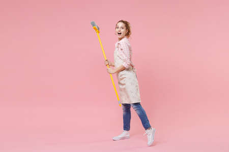 Excited funny young woman housewife in casual clothes, apron doing housework isolated on pastel pink wall background studio portrait. Housekeeping concept. Mock up copy space. Hold in hands broom.