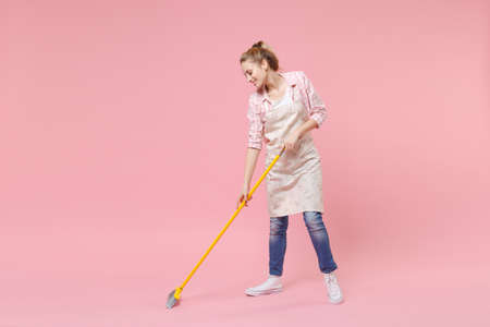 Smiling pretty young woman housewife in casual clothes, apron doing housework isolated on pastel pink wall background studio portrait. Housekeeping concept. Mock up copy space. Sweeping with broom. Standard-Bild