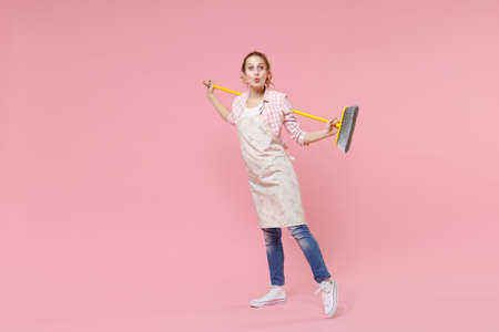 Amazed pretty young woman housewife in casual clothes, apron doing housework isolated on pastel pink wall background studio portrait. Housekeeping concept. Mock up copy space. Hold in hands broom. Standard-Bild
