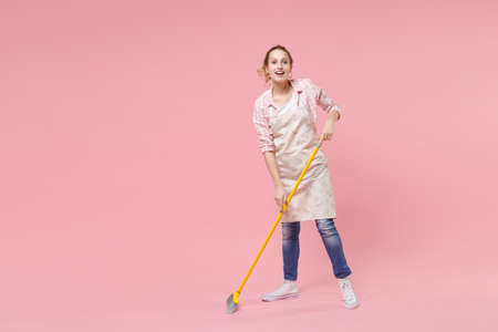 Cheerful funny young woman housewife in casual clothes, apron doing housework isolated on pastel pink wall background studio portrait. Housekeeping concept. Mock up copy space. Sweeping with broom.