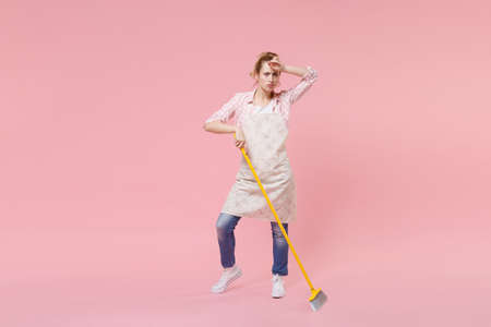 Tired young woman housewife in casual clothes, apron doing housework isolated on pastel pink background studio portrait. Housekeeping concept. Mock up copy space. Sweeping with broom put hand on head.