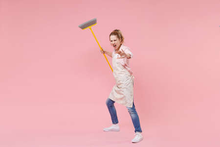 Irritated woman housewife in casual clothes apron doing housework isolated on pink background. Housekeeping concept. Mock up copy space. Sweeping with broom screaming showing stop gesture with palm. Standard-Bild