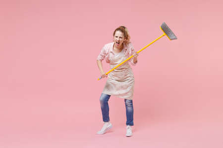 Angry young girl housewife in casual clothes apron doing housework isolated on pastel pink background studio portrait. Housekeeping concept. Mock up copy space. Sweeping with broom screaming swearing.