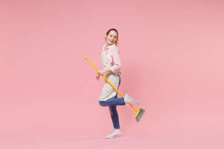 Cheerful pretty young woman housewife in casual clothes, apron doing housework isolated on pastel pink wall background studio portrait. Housekeeping concept. Mock up copy space. Hold in hands broom.