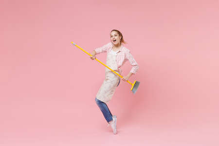 Funny young woman housewife in casual clothes, apron doing housework isolated on pastel pink background studio portrait. Housekeeping concept. Mock up copy space. Dancing with broom, standing on toes. Standard-Bild