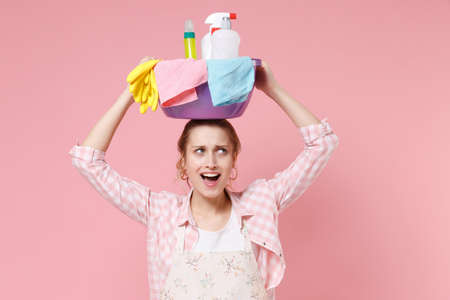Excited young woman housewife in apron doing housework isolated on pastel pink background studio. Housekeeping concept. Holding basin with detergent bottles washing cleansers on head looking up aside.