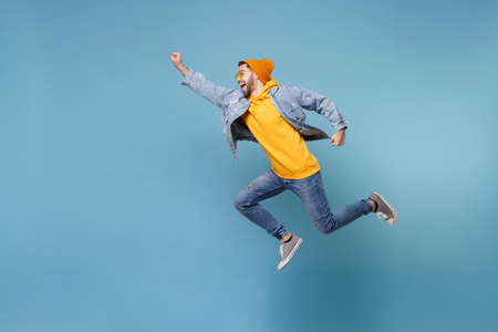 Side view of young hipster guy in fashion jeans denim clothes posing isolated on pastel blue background. People lifestyle concept. Mock up copy space.