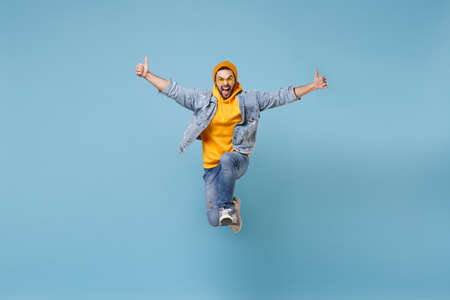 Crazy young hipster guy in fashion jeans denim clothes posing isolated on pastel blue background studio portrait. People lifestyle concept. Mock up copy space. Jumping, screaming, showing thumbs up.