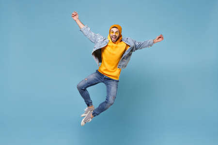 Excited young hipster guy in fashion jeans denim clothes posing isolated on pastel blue wall background studio portrait. People emotions lifestyle concept. Mock up copy space. Jumping spreading hands.