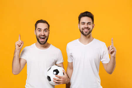 Excited men guys friends in white t-shirt posing isolated on yellow background. Sport leisure concept. Mock up copy space. Cheer up support favorite team with soccer ball pointing index finger up.