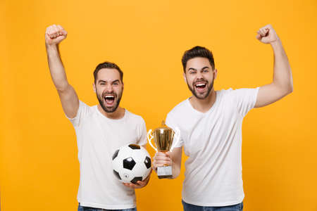 Two men guys friends in white t-shirt isolated on yellow background. Sport leisure lifestyle concept. Cheer up support favorite team with soccer ball football cup, expressive gesticulating with hands.