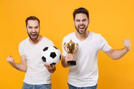 Two men guys friends in white t-shirt posing isolated on yellow background. Sport leisure concept. Mock up copy space Cheer up support favorite team with soccer ball football cup doing winner gesture.
